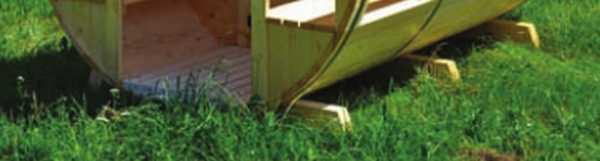 Можно поставить баню-бочку на ровный участок почвы, покрытый травой